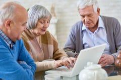 Les personnes âgées à l'aide de l'ordinateur portable dans la maison de repos Photographie stock libre de droits
