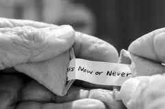 Les personnes âgées équipe des mains tenant le message de biscuit de fortune Photos libres de droits