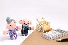 Les personnes âgées avec le fauteuil roulant et la calculatrice sur le fond blanc Photographie stock libre de droits