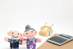 Les personnes âgées avec le fauteuil roulant et la calculatrice sur le fond blanc Photos stock