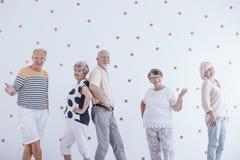 Les personnes âgées célébrant la veille du ` s de nouvelle année contre l'esprit blanc de mur Photographie stock libre de droits