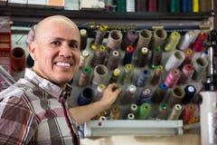 Les personnes âgées de sourire travaillent avec les bobines colorées du fil Images stock