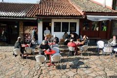 Les personnes âgées et d'autres personnes s'asseyent aux tables de café sur la rue avec les bâtiments historiques Photographie stock