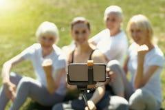 Les personnes âgées et entraîneur posant pour le selfie dehors photo stock