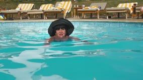Les personnes âgées féminines supérieures caucasiennes dans un chapeau nage dans une piscine d'eau bleue dans un hôtel Contre le  banque de vidéos