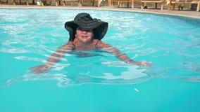 Les personnes âgées féminines supérieures caucasiennes dans un chapeau nage dans une piscine d'eau bleue dans un hôtel Le concept clips vidéos