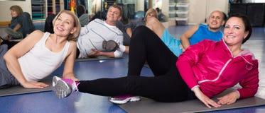 Les personnes âgées faisant l'exercice sur le tapis dans le gymnase moderne photos stock