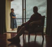 Les personnes âgées ménage à la maison, le mari s'assied à l'intérieur sur le fauteuil, l'épouse se tient sur le balcon et regard Photo stock