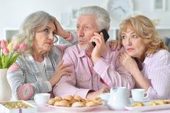 Les personnes âgées prenant le petit déjeuner et à l'aide du téléphone portable Image stock