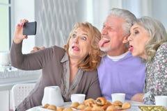 Les personnes âgées prenant le petit déjeuner et à l'aide du téléphone portable Images stock