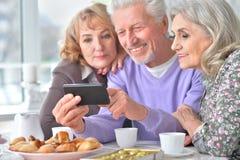 Les personnes âgées prenant le petit déjeuner et à l'aide du téléphone portable Images libres de droits