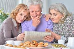 Les personnes âgées prenant le petit déjeuner et lisant un journal Photos libres de droits