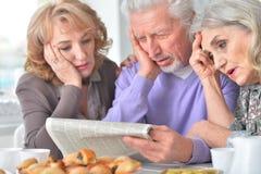 Les personnes âgées prenant le petit déjeuner et lisant un journal Photographie stock