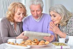 Les personnes âgées prenant le petit déjeuner et lisant un journal Photo libre de droits