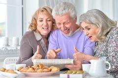Les personnes âgées prenant le petit déjeuner et lisant un journal Photo stock