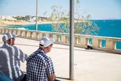 Les personnes âgées s'asseyant au point de vue dans Albufeira et observant la mer d'Algarvian Photo libre de droits