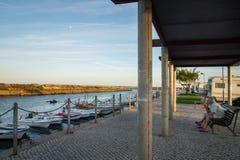 Les personnes âgées s'asseyant au point de vue dans Fuseta et lagune de observation dans le coucher du soleil, Algarve, Portugal Photographie stock libre de droits
