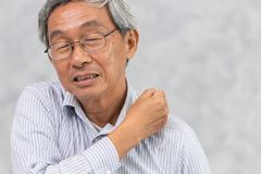 Les personnes âgées soutiennent la douleur de cou et d'épaule utilisant la main pour masser photos stock