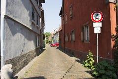 Les personnes allemandes conduisant la voiture de sport rouge viennent dans la petite allée Photos stock
