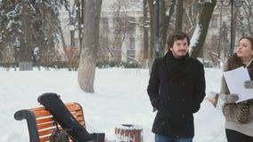 Les personnes attirantes ont une conversation dans le parc d'hiver clips vidéos