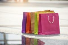 Les personnes de client ont placé les sacs à provisions colorés après l'achat de finition au mail de mode Le cadeau et le présent photos libres de droits