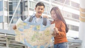 Les personnes de couples de voyageur emploient la carte locale générique et parlent à c urbain Images libres de droits