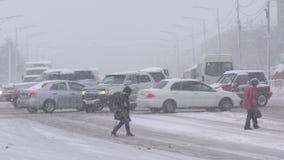 Les personnes de groupe traversent la route urbaine au passage pour piétons pendant le snowstormblizzard banque de vidéos