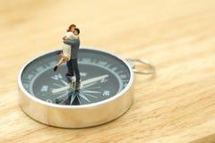 Les personnes de la miniature 2 de couples se tenant sur une boussole communiquent la direction des couples utilisation en tant q images libres de droits