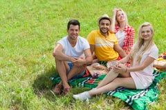 Les personnes de pique-nique d'amis groupent l'herbe verte extérieure couvrante se reposante Photographie stock