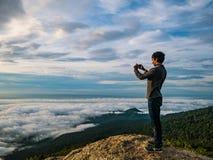 Les personnes de silhouette prennent une photo sur la falaise avec le beau ciel de lever de soleil sur la montagne de Khao Luang photo stock