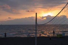 Les personnes de silhouettes au fond de coucher du soleil Photographie stock libre de droits