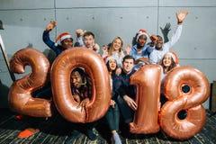 Les personnes de sourire heureuses tenant le nombre d'or montent en ballon, symbole de 2018 ans Images stock