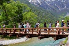 Les personnes de touristes augmentant le Kappa Bashi jettent un pont sur la rivière, Kamikochi, Japon Photo stock