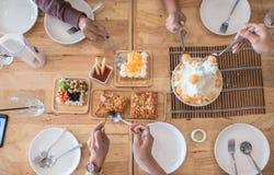 Les personnes de vue supérieure mangent le dessert de repas Les amis et la famille célèbrent avec la nourriture sur la table en b Photographie stock