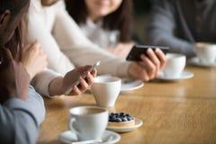 Les personnes diverses à l'aide des smartphones à la table de café, se ferment vers le haut de la vue Photos stock