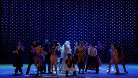 Les personnes extraordinaires dans des costumes scéniques dansent sur l'étape dans le théâtre banque de vidéos