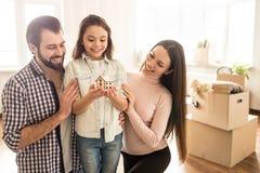 Les personnes gaies et heureuses regardent à la petite maison de jouet que la petite fille tient Elle des parents sourient et Photo stock