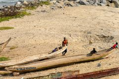 Les personnes ghanéennes non identifiées se reposent sur des canoës sur la côte de l'orme images libres de droits