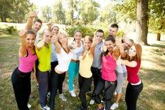 Les personnes heureuses avec des pouces lèvent le signe Image libre de droits