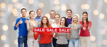 Les personnes heureuses avec la vente rouge signent montrer des pouces  Photos libres de droits