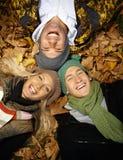 Les personnes heureuses en automne stationnent la pose parmi des lames Image stock