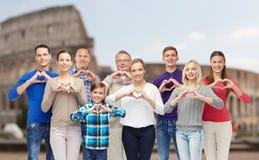 Les personnes heureuses montrant la main de coeur signent plus de le Colisé Photo stock