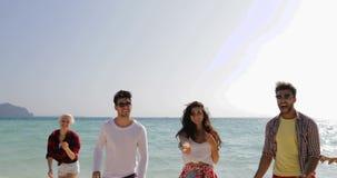 Les personnes heureuses sur la plage courue pour arroser, les hommes gais de course de mélange et les touristes sautants de group clips vidéos