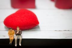 Les personnes miniatures, couples aiment s'asseoir sur une table en bois avec le fond rouge de coeur copiez l'espace utilisant co Image libre de droits