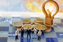 Les personnes miniatures, homme d'affaires pensent avec l'idée de lampe sur le coi Photographie stock libre de droits