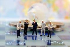 Les personnes miniatures, homme d'affaires pensent avec le globe sur les pièces de monnaie s photographie stock