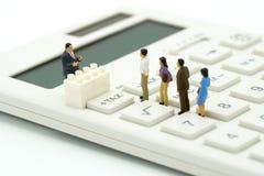 Les personnes miniatures payent à file d'attente l'IMPÔT SUR LE REVENU annuel pendant l'année sur la calculatrice utilisation en  photos libres de droits
