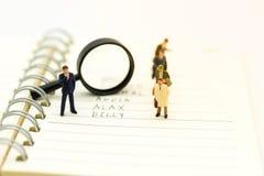 Les personnes miniatures, surveillants recherchent des employés pour la mise en place d'offres, employant comme choix de fond de  Image stock