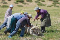 Les personnes mongoles roulent le feutre en steppe dans Harhorin, Mongolie photographie stock