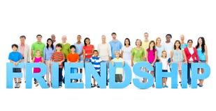 Les personnes multi-ethniques tenant l'amitié marquent avec des lettres le concept Image stock
